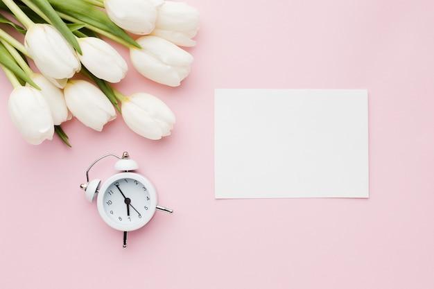 Flores de tulipán con reloj y papel vacío