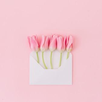 Flores de tulipán en sobre en mesa
