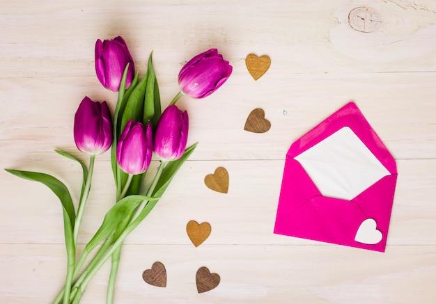 Flores de tulipán con sobre y pequeños corazones.