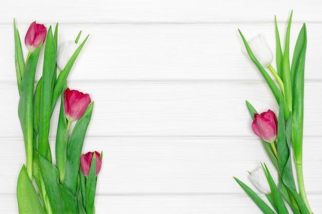 Flores de tulipán sobre tablas de madera pintadas de blanco. copie el espacio. fondo floral del marco de la primavera