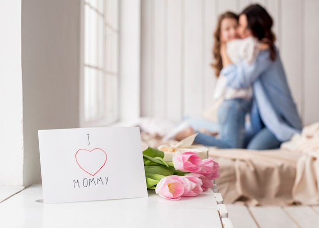 Flores de tulipán y tarjeta de felicitación en mesa