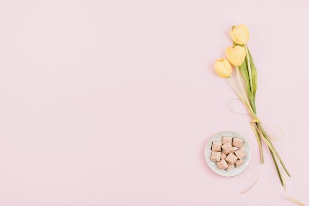Flores de tulipanes amarillos y chocolate rosa sobre fondo pastel. cumpleaños festivo plano lay
