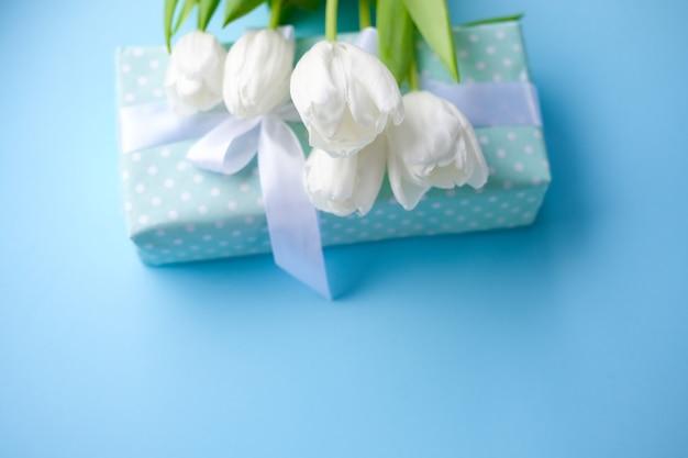 Flores de tulipanes blancos y caja de regalo sobre fondo azul.