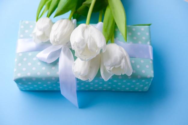 Flores de tulipanes blancos y caja de regalo sobre superficie azul