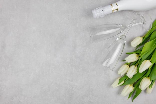 Flores de tulipanes blancos con champán, copas de vino y caja de regalo sobre superficie de hormigón gris claro