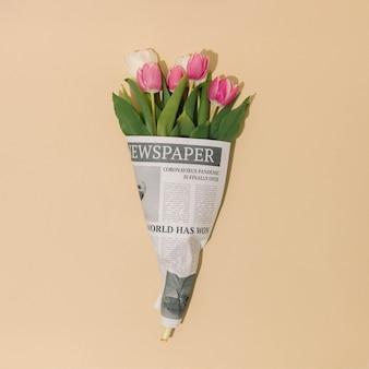 Las flores de tulipanes de primavera envueltas en periódicos con pandemia global están sobre los titulares