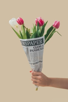 Flores de tulipanes de primavera envueltas en periódicos con titular de pandemia mundial
