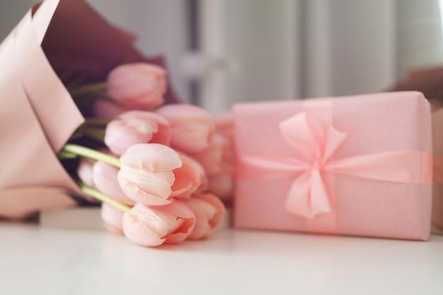 Flores de tulipanes rosados y regalo o caja presente fondo rosa. día de la madre, cumpleaños, día de san valentín, día de la mujer, concepto de celebración. espacio para texto.