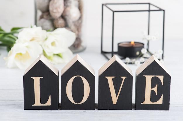 Flores y velas encendidas y carta de madera amor