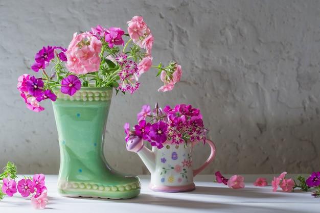 Flores de verano en bota de cerámica en blanco