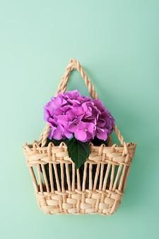 Flores de verano en cesta de paja en turquesa con espacio de copia.