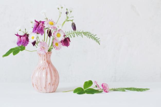 Flores de verano en florero rosa sobre fondo blanco.