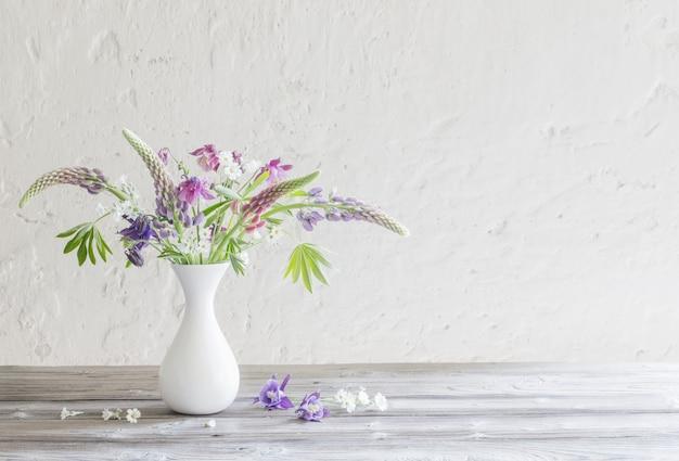 Flores de verano en florero sobre fondo de pared blanca