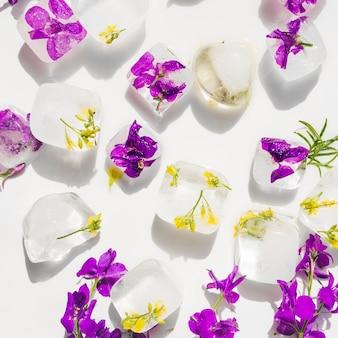 Flores violetas y amarillas en cubitos de hielo.
