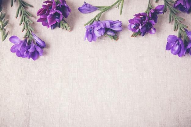 Flores violetas azules sobre lino
