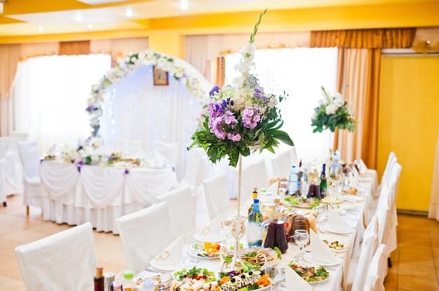 Flores violetas lilas en mesa de boda