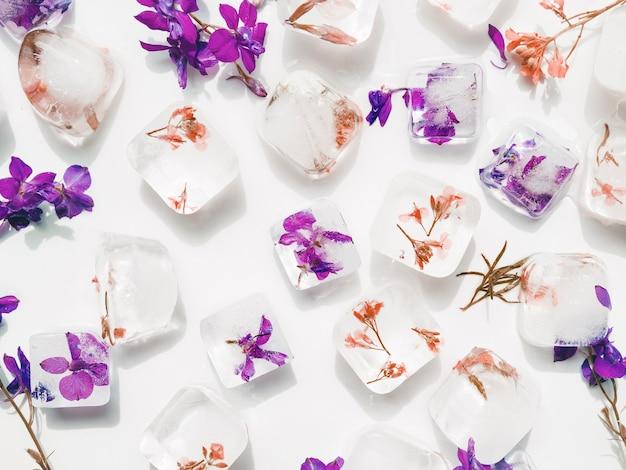 Flores violetas y rojas en cubitos de hielo.