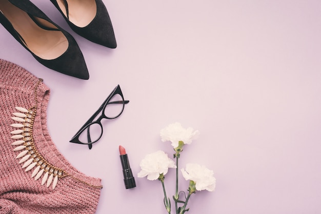 Flores con zapatos de mujer, pintalabios, collar y suéter.
