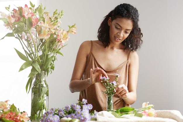 Florista africano alegre hermoso de la mujer que sonríe haciendo el ramo en floristería sobre la pared blanca.