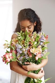 Florista africano de la mujer que sonríe sosteniendo el ramo el oler de alstroemerias sobre la pared blanca. ojos cerrados.