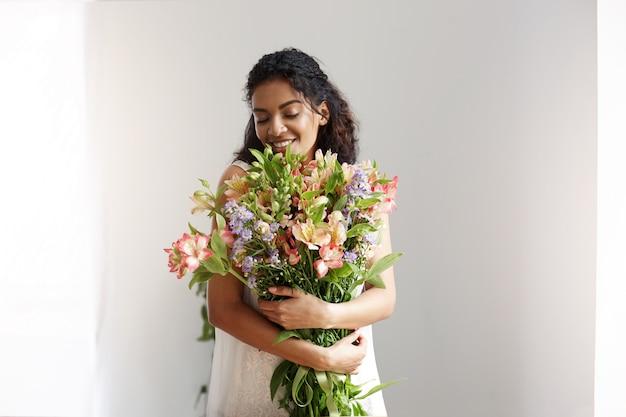 Florista africano tierno de la mujer que sonríe sosteniendo el ramo de alstroemerias sobre la pared blanca. ojos cerrados.