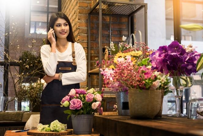Florista de pie en su floristería y usando su teléfono para recibir pedidos de su tienda