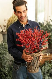 Florista experimentado sonríe y sostiene plantas rojas