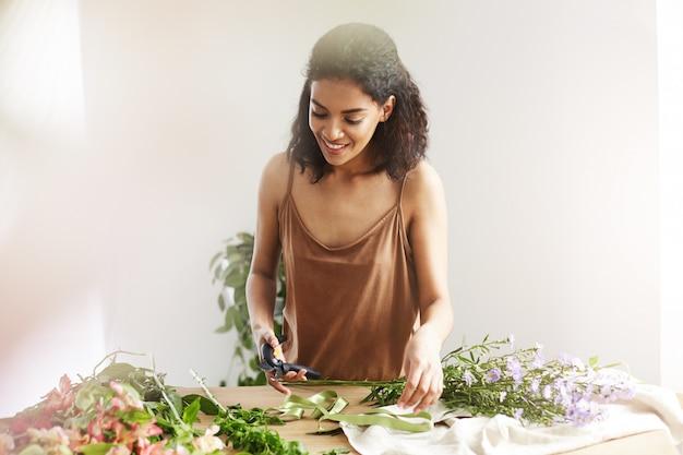 El florista femenino africano atractivo que sonríe cortando tallos que trabajan en floristería sobre la pared blanca.