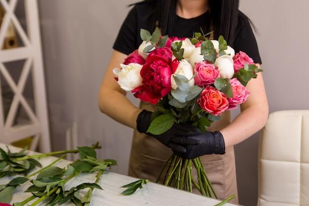 Florista en guantes negros crea un ramo de peonías rojas