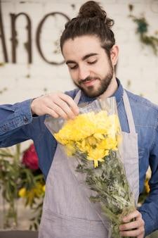 Un florista masculino envolviendo las flores de crisantemo amarillo en el papel de plástico