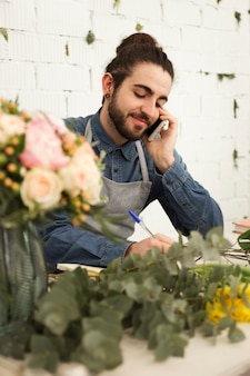 Florista masculino joven que observa orden del cliente durante la conversación del teléfono móvil en floristería