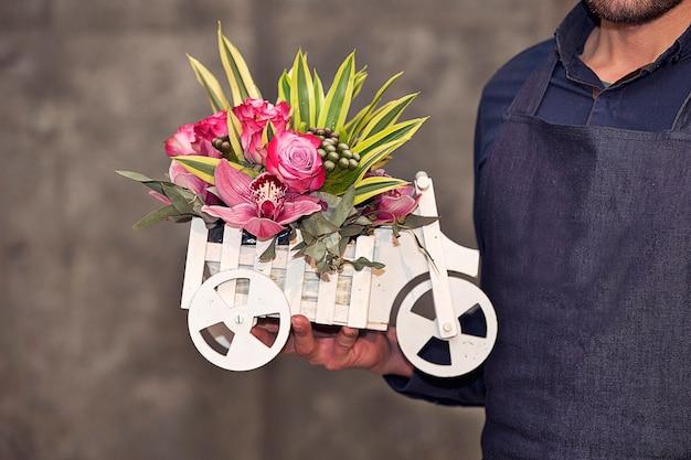 Florista masculino promocionando una cesta de flores mixtas en forma de coche.