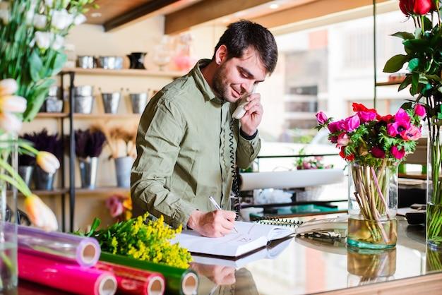 Florista masculino que acepta pedidos por teléfono en una florería