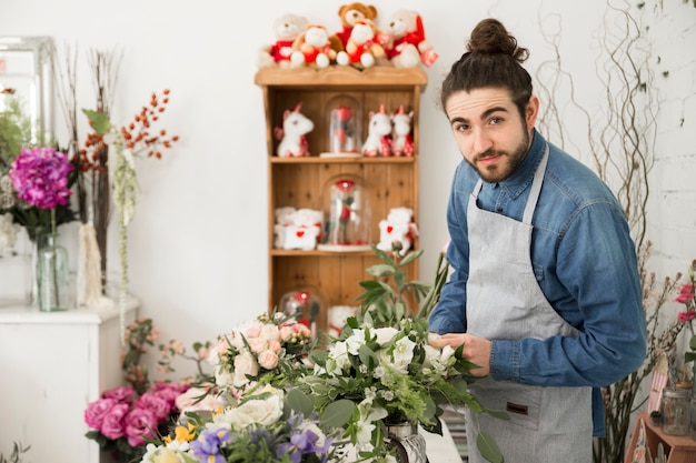 Un florista masculino que crea el ramo de flores en su tienda.