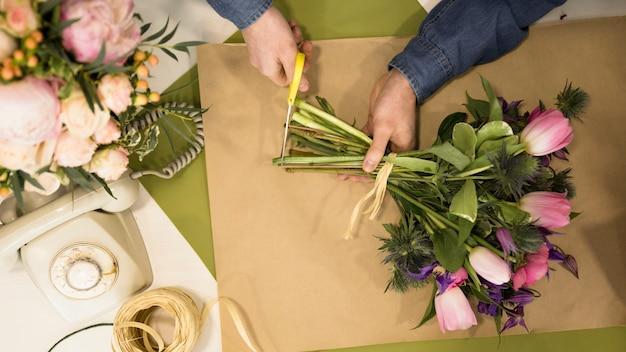 Un florista masculino que poda el tallo del ramo de flores en la floristería.