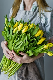 Florista de la muchacha que sostiene un manojo de tulipanes amarillos. floristica fondo gris