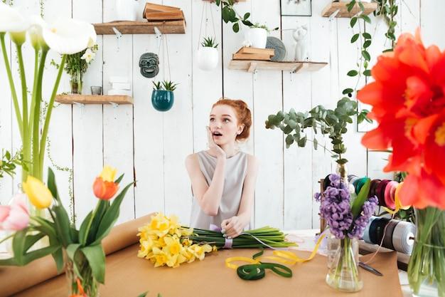 Florista mujer sorprendida mirando a un lado mientras está sentado entre flores