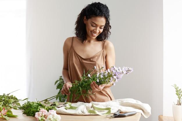 Florista de sexo femenino bastante africano que sonríe haciendo el ramo en el lugar de trabajo sobre la pared blanca.