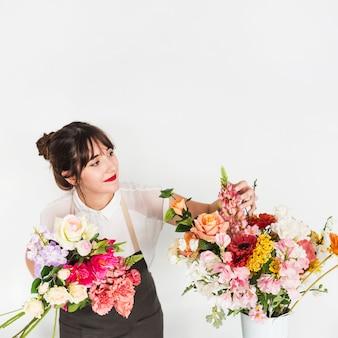Florista de sexo femenino que mira las flores en el fondo blanco