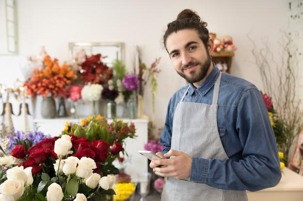 Florista de sexo masculino joven feliz que sostiene el teléfono móvil en la mano que mira a la cámara
