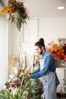 Florista de sexo masculino joven sonriente que cuida de las flores en el ramo