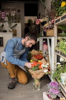 Florista de sexo masculino que mira el ramo rojo hermoso del tulipán en la tienda