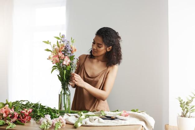 Floristería africana hermosa de la mujer que sonríe haciendo el ramo de flores. pared blanca.