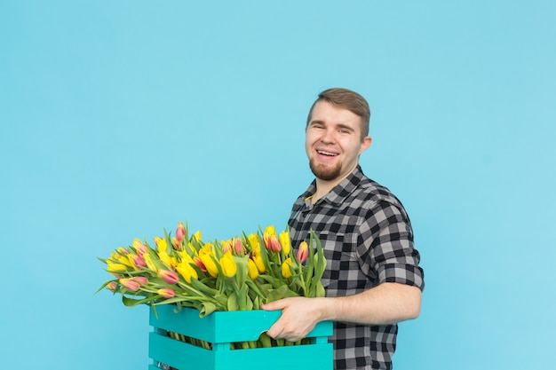 Floristería alegre guapo sosteniendo una caja de tulipanes en la pared azul,