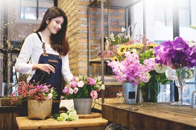 Floristería del dueño de negocio de las mujeres jovenes que hace el ramo delante de la floristería.