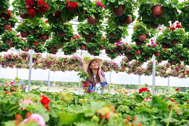 Floristería encantadora mujer cuidando de flores en invernadero y disfrutando de su trabajo