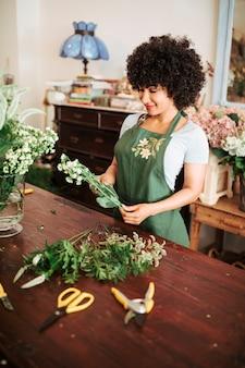 Floristería femenina africana feliz que mira el manojo de flores blancas en tienda
