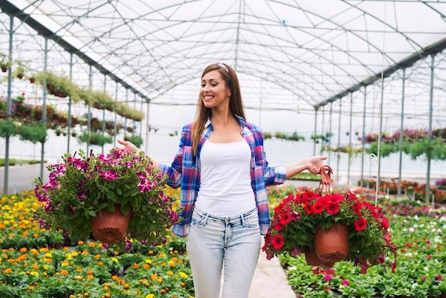 Floristería femenina llevando plantas de flores en macetas en invernadero organizarlos para la venta