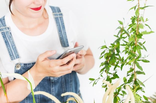Floristería femenina utilizando un teléfono móvil cerca de las plantas.