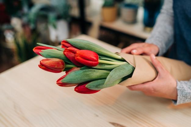 Floristería hace ramo de tulipán rojo y envolver en papel de paquete en mesa de madera